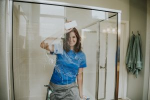 House cleaning technician cleaning shower glass