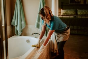 House cleaner cleans the bathtub with glove and a mask